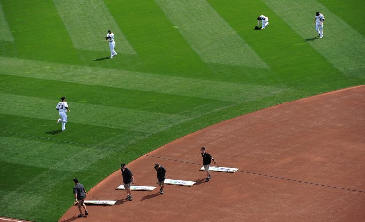 The grounds crew makes a last sweep of the infield. (Rebecca Droke/Post-Gazette)