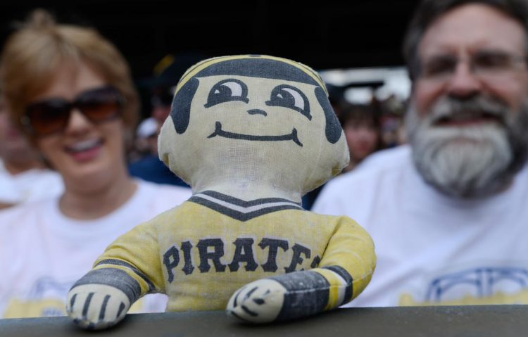 Lou Ann and Mark McDonnell of Churchill with their Pirates doll, that they have been bringing to games since the 1970's. (Rebecca Droke/Post-Gazette)