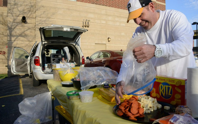 """Sean Flanagan , of Bellaire, Ohio, empties bags of cheese and pepperoni as he gets ready for a """"tailgate party"""" of 25 , in a lot near  PNC Park before the Pirates Home Opener (Darrell Sapp/Post-Gazette)."""