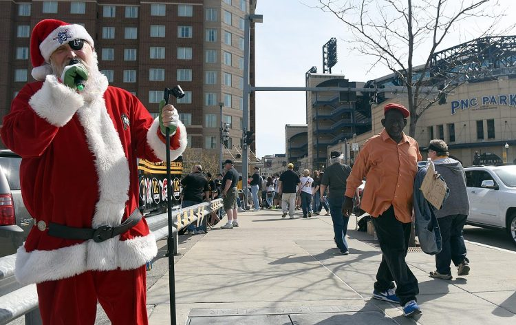 """Marion Mays of Oakland dressed as Santa and sang """"Riders on the Storm,"""" despite the sunny 70-degree weather. (Steve Mellon/Post-Gazette)"""