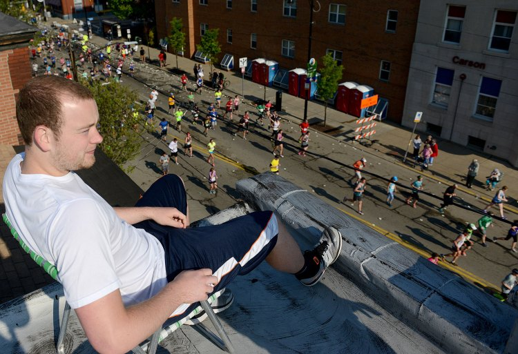 Chad Nowak of the South Side watches from the roof of an apartment building on Carson Street. (Michael Henninger/Post-Gazette)