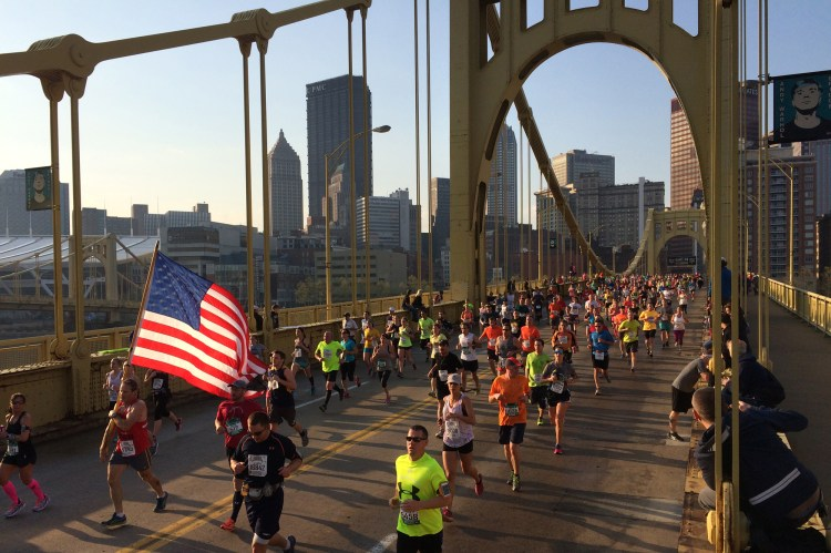 A flag-waving runner makes his way across the Andy Warhol Bridge. (Steve Mellon/Post-Gazette)