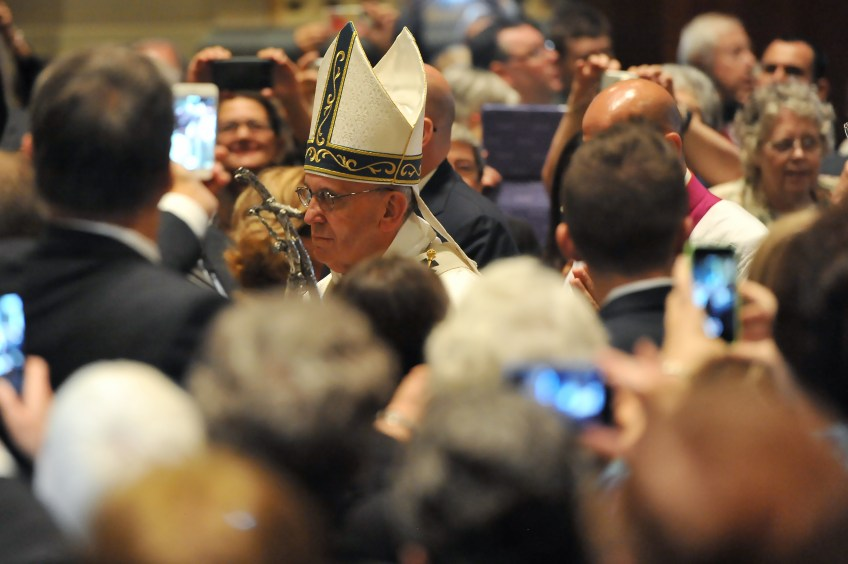 After he dresses for Mass, Pope Francis once again processes down the main aisle as people take pictures and video at the Cathedral Basilica of Saints Peter and Paul in Philadelphia on Saturday.