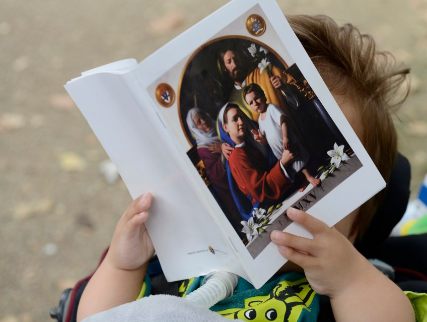 Andrew Farrell, 20 mos., holds a program for the open air Mass along the Benjamin Franklin Parkway in Philadelphia on Sunday, Sept. 27. The Mass was the final event of Pope Francis' visit to the United States. (Rebecca Droke/Post-Gazette)