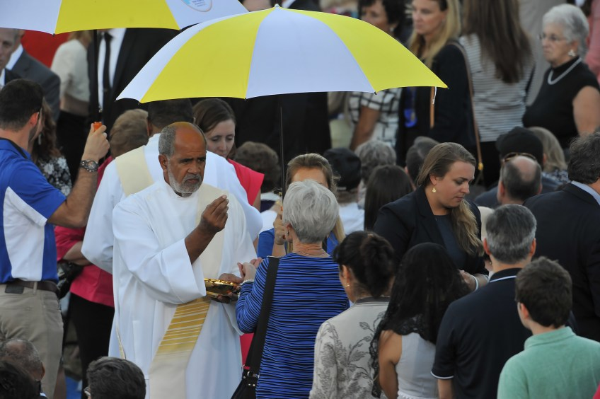 A priest gives communion during the canonization Mass for Junipero Serra at the Basilica of the National Shrine of the Immaculate Conception on Wednesday.