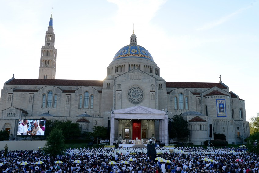 Priests escorted by umbrella-carrying volunteers disperse throughout the crowd to give communion during the canonization Mass for Junipero Serra at the Basilica of the National Shrine of the Immaculate Conception on Wednesday.