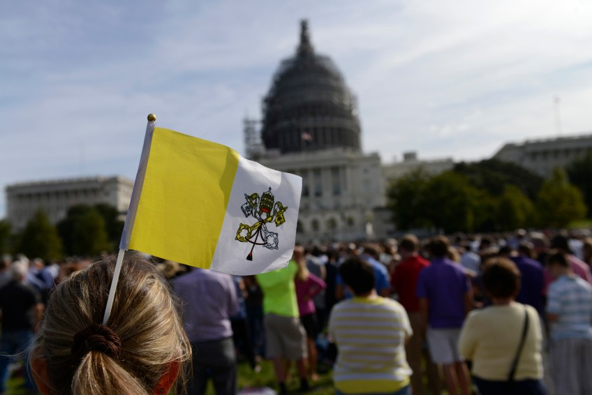 A woman sticks the Vatican Flag into her hair as she watches Pope Francis address Congress from the West Front Lawn in Washington, D.C. on Thursday.