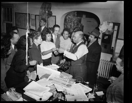 "P.L. Prattis, (center, in vest) and staff gather in the Pittsburgh Courier newsroom in the mid-1940s. ( © Carnegie Museum of Art, Charles ""Teenie"" Harris Archive )"