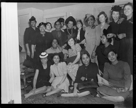 """Edith McColes Whitaker, center of the back row, wears a large hat and a necklace of pearls at a ladies luncheon held at Julia Calloway's Mooseheart Street Home, 1941. She was the grandmother of Mark Whitaker, author of """"Smoketown."""" The women in this picture are Nellie Kent, Mary Harris, Frances Johnson, Carol Williams, Carrie Rieck, Ann Hale, Lillie Mae Penn, Jeraldine Porter, Hazel Betters, Urshe Kincaide, Marie Winters, Catherine Streeter Wilson, Bessie Jackson, Abbie McCloud, Julia Calloway wearing key brooch, and Lil Mae Surcey. ( © Carnegie Museum of Art, Charles """"Teenie"""" Harris Archive )"""