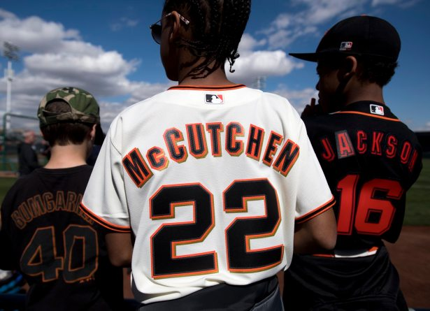 Wearing his custom-made jersey, William Calhoun, 13, of Oakland, Calif., waits to see Andrew McCutchen take the field for his first spring training game with the Giants. (Steph Chambers/Post-Gazette)