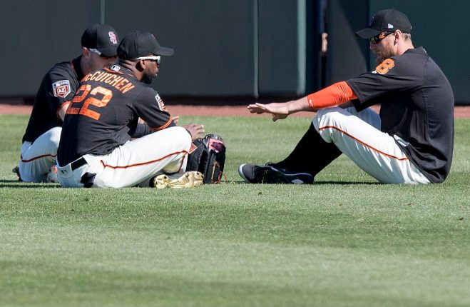 Outfielders Austin Slater, Andrew McCutchen and Hunter Pence pretend to sit around a fire during a spring training drill. (Steph Chambers/Post-Gazette)