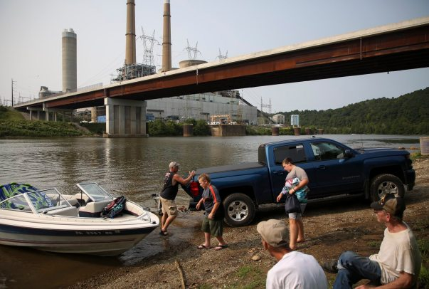 From left Greg Brown along with Braedyn Wasko and Brown's son Josh Ochkie prepare to launch a boat into the Monongahela River across from the shuttered Hatfield's Ferry Power Station coal-fired plant on Aug. 19. (Jessie Wardarski/Post-Gazette)