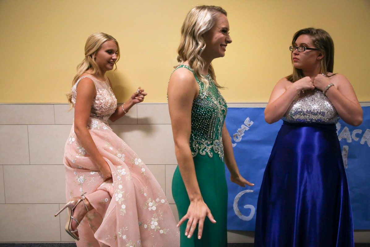 From left Abigail Claire Rocks, Micaela Ricco, and Sara Ann Hornick make last-minute adjustments to their evening gowns as they wait to compete in the 65th Annual State Bituminous Coal Queen Pageant on Aug. 19. (Jessie Wardarski/Post-Gazette)