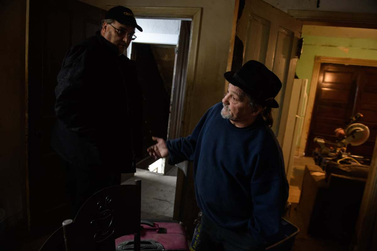 "Chaplain of the ARK Allegheny Recovery Krew Rev. Jay Geisler of St. Peter's Episcopal Church in Brentwood, left, and ARK recovery director Gus DiRenna talk in a former drug house on Thursday, Nov. 15, 2018, in Carrick. Both men are in recovery and are helping others through the creation of this and other ""Serenity Houses."""