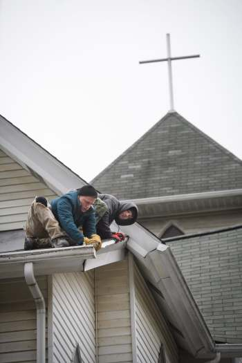 Shawn Wypych, left, 24, of Carrick, and Justin Arnold, 30, of Whitehall, secure Christmas lights to the roof edge at Fairhaven United Methodist Church on Wednesday, Nov. 21, 2018, in Carrick. The men gather for breakfast at the church every morning, pray, and talk about recovery before heading to work with the ARK Allegheny Recovery Krew.