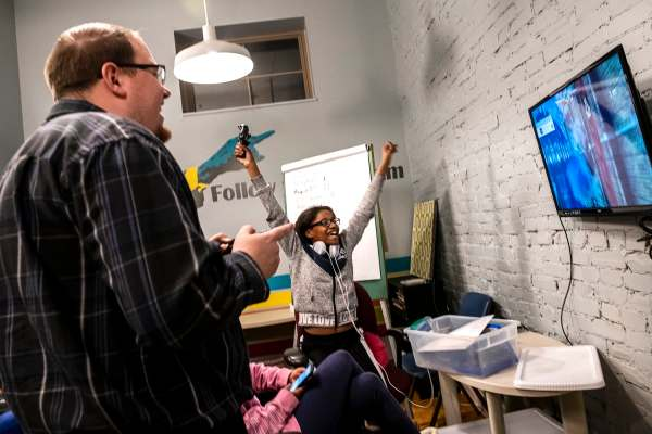 Greg Hummel, left, of Sellersburg and a volunteer with Volunteers of America, laughs as Danielle Washington celebrates after winning a video game during the Teens with a Purpose program, Thursday, Jan. 24, 2019, at Transitional Housing Program & Emergency Family Shelter in Louisville, Ky. The Teens with a Purpose program meets weekly to give teens living in the shelter a space to interact with each other and volunteers. Volunteers of America offers solutions that help to try and prevent homelessness with services that include eviction prevention, emergency services, transitional housing and permanent affordable housing.