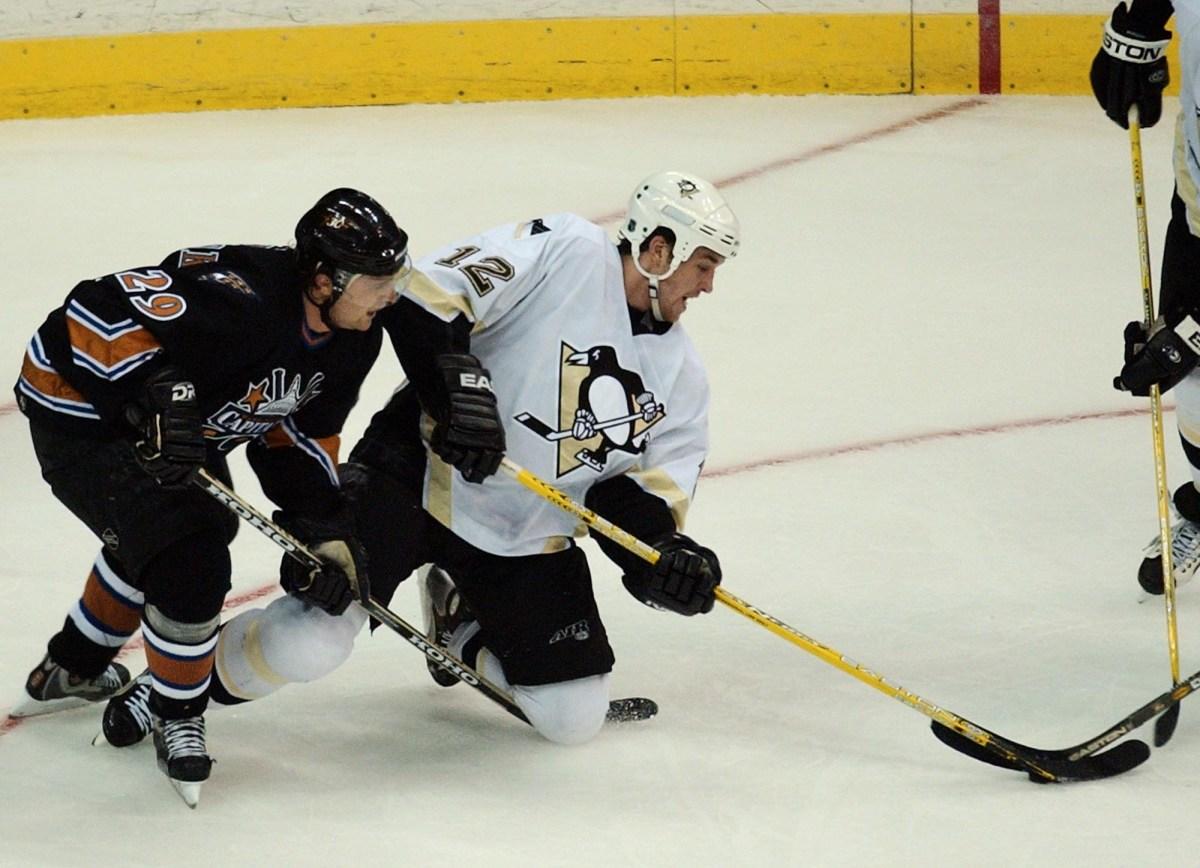 Penguins forward Ryan Malone battles for the puck with Washington Capitals defenseman Joel Kwiatkowski in the second period in Washington, Tuesday, March 30, 2004. (Gerald Herbert/Associated Press)