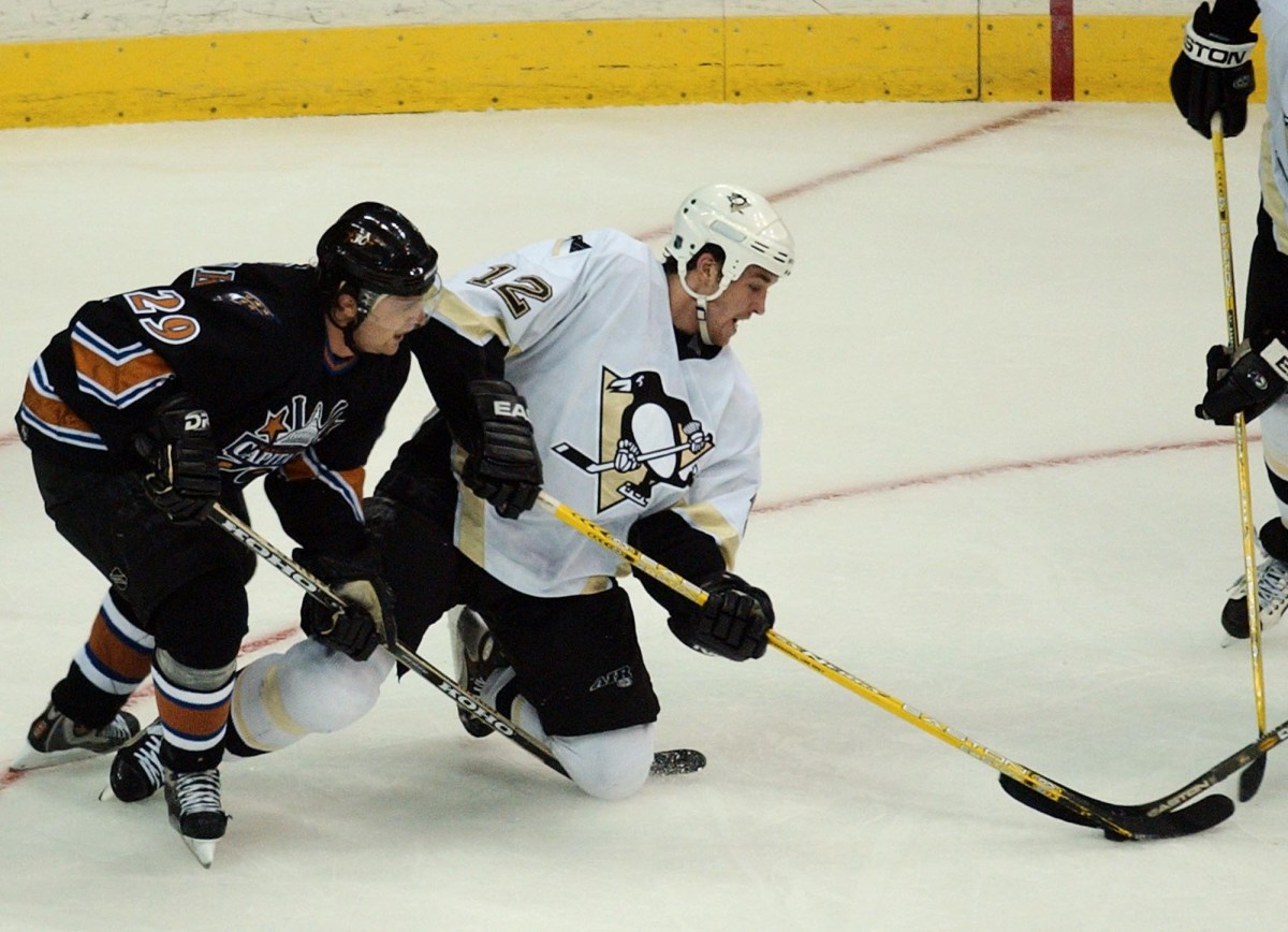 Penguins forward Ryan Malone battles for the puck with Washington Capitals defenseman Joel Kwiatkowski in the second period in Washington, Tuesday, March 30, 2004. (Gerald Herbert/Associated Press)