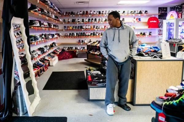 "Mark Pence looks in the mirror to see how a sneaker looks on him, Thursday, Jan. 24, 2019, in Louisville, Ky. ""I buy shoes because I just want to feel youthful. I didn't really have a childhood, I was too busy helping to raise a household."" At one point, with his mother working and going to school, Pence was taking care of his younger brothers, which he feels left him out of having a real childhood. Pence is a member of the Louisville Youth Action Board at the Coalition for the Homeless. His experiences with chronic homeless led to his advocacy work."