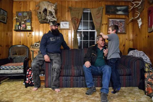 Ben Brown, left, 34, watches as his son Oliver, right, 7, roughhouses with his father-in-law, Douglas Basinger, 63, who came to say goodnight to the children at the Browns' home, Thursday, Jan. 3, 2019, at the family farm in Saltlick and Bullskin. Basinger and his wife, who live in a neighboring home, are a critical part of helping to care for the children as Brown's wife deals with the fatigue, pain, and side effects of treatment from breast cancer.