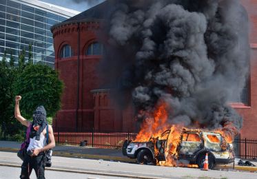 A police vehicle burns outside of PPG Paints Arena during a protest against police brutality, Saturday, May 30, 2020, in Downtown. The protest began with about 1,000 people marching to honor George Floyd, who was killed in police custody in Minneapolis five days prior. (Emily Matthews/Post-Gazette)