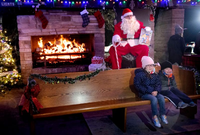 Siblings Aubrey, left, 5, and Styles Davies, 3, get a socially distant photo taken with Santa during the Moon Lights Holiday Festival, Saturday, Dec. 5, 2020, at Moon Park in their neighborhood of Moon Township. (Emily Matthews/Post-Gazette)