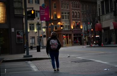 A pedestrian on an empty Wood Street at dusk, Tuesday evening, March 17, 2020, in Downtown. Many businesses, schools and government offices closed or informed employees to work from home over concerns about COVID-19. (Steve Mellon/Post-Gazette)