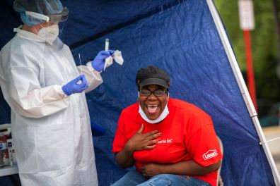 Emily Entwistle, medical assistant for Allegheny Health Network, left, prepares swatches as Nickole Nesby, mayor of Duquesne, right, reacts after experiencing a COVID-19 test at a Allegheny Health Network (AHN) mobile clinic, Friday, May 29, 2020, in Duquesne. AHN's mobile COVID-19 testing unit is part of an initiative to bring testing to underserved communities. The mobile test site has previously been set up in Homewood and the Hill District. (Michael M. Santiago/Post-Gazette)