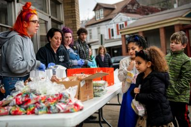 Nora Peters, left, of Millvale, a volunteer with the Northern Area Boys and Girls Club, gives out lunches to sisters Amber, 10, center, and Justice Long, 6, second from right, along with Sylas Schivins, 9, all of Shaler, Tuesday, March, 17, 2020, at Holy Spirit Parish in Millvale. The Shaler Area school district will provide free grab-and-go breakfast to any Shaler Area student age 18 and younger each weekday due to the closing of the schools because of COVID-19. (Michael M. Santiago/Post-Gazette)