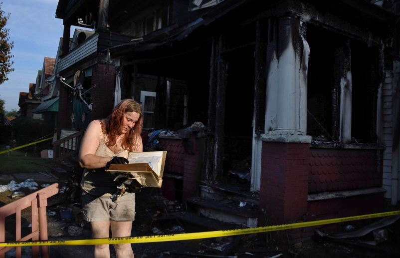 Jaime Confer looks through her mother's Bible after finding it in a box in the remains of her charred home early morning, Tuesday, June 23, 2020, in Vandergrift. (Darrell Sapp/Post-Gazette)