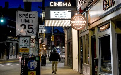 """A sign of hope from the Row House Cinema along Butler Street, Monday, March 16, 2020, in Lawrenceville. As Allegheny County encouraged the closing of any non-essential businesses, the theater closed """"for the foreseeable future."""" The theater's sister store next door, Bierport, offered Curb Side Service of popcorn, beer and candy to go. (Darrell Sapp/Post-Gazette)"""