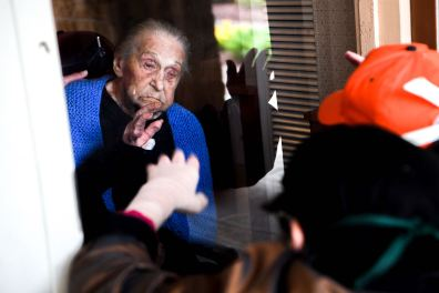 Mollie, 100, waves to her daughter Janice, who did not want either of them to be identified by last name, while they visited through a plexiglass barrier on Mother's Day, Sunday, May 10, 2020, at the Jewish Association on Aging in Squirrel Hill. (Alexandra Wimley/Post-Gazette)