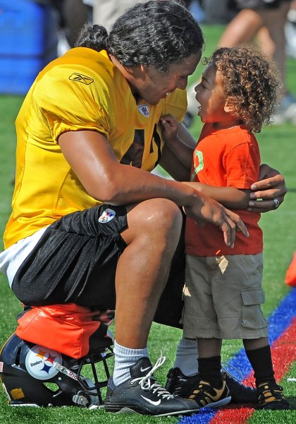 Troy Polamalu laughs with his son between workouts at training camp