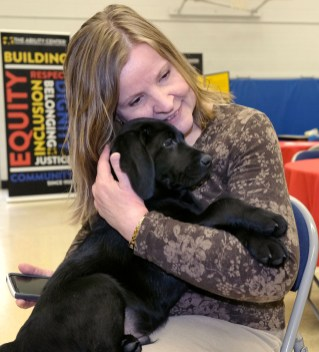ADAI employee Kristina Irvin hugs a Labrador Retriever puppy during a Special Auxiliary Play Date for invited guests at the Ability Center in Sylvania. THE BLADE/LORI KING