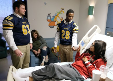 Whitmer High School football player Chris Redway, left, watches Pasean Wimberly give a football to Laila Rivers, 14, a Whitmer student, during a visit to St. Vincent Mercy Children's Hospital in Toledo on March 11, 2019. The visit was coordinated through the Toledo Wistert Chapter of the National Football Foundation. THE BLADE/LORI KING CTY VISIT12