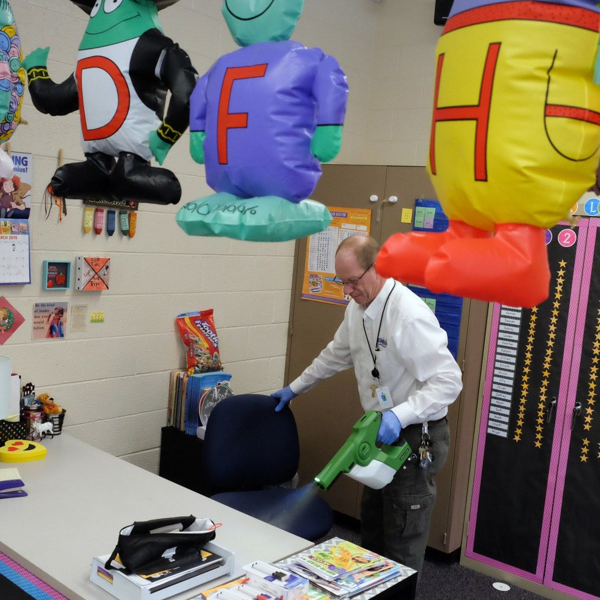 Cris Myers uses a Victory Innovations sprayer in a kindergarten classroom. Cris (cq) Myers (cq), manager, building maintenance services for CorpClean (cq), working at Christ the King School after a flu outbreak forced the closure of the school in Toledo, Ohio on March 6, 2019. He uses an electrostatic spray gun which atomizes and electro-statically charges the cleaning solution so it encapsulates whatever it's sprayed on. THE BLADE/JETTA FRASER