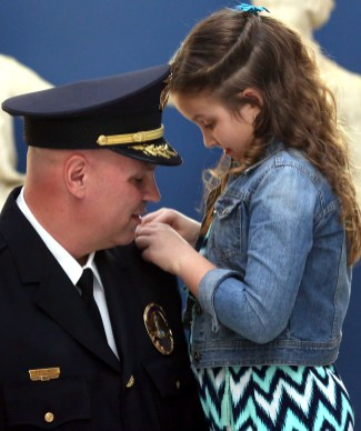 Patrick Jones, the newly appointed police chief, has one of his rank insignias pinned on his uniform by his 8-year-old daughter Gabriella Jones after he was sworn in at Perrysburg City Hall in Perrysburg, Ohio, on Tuesday, April 16, 2019. THE BLADE/KURT STEISS CTY PERRYSBURG17