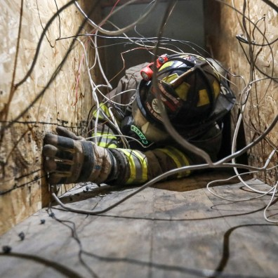 Andrew Slife of Perrysburg Township Fire Department feels his way through cords and wires as part of a training exercise for BGSU's State Fire School in Toledo, Ohio on Monday May 20, 2019. Firefighters are blindfolded as they feel their way through a course to help with problem solving skills when they are in the field. THE BLADE/REBECCA BENSON CTY fireschool20p