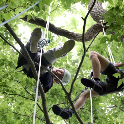 Camper Lucas Polkinghorn, 12, of Maumee, smiles at another camper in the tree during tree climbing camp at Oak Openings Preserve on Monday, June 24, 2019. THE BLADE/AMY E. VOIGT
