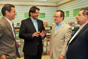 Vita Natura President Frank Medina (center) chats with executives who joined him for the Roosevelt Avenue store opening Tuesday.