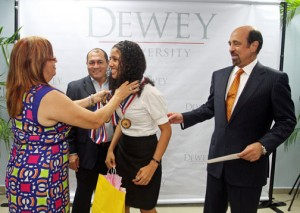 One of this year's outstanding students receives an achievement medal, as  Dewey University President Carlos Quiñones-Alfonso (right) looks on.