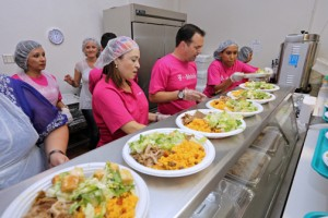 T-Mobile employees line up the plates of typical Puerto Rican Christmas fare for the annual lunch at La Fondita de Jesús.