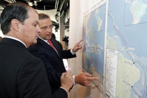 Claro President Enrique Ortiz de Montellano and Gov. García-Padilla check out the map showing the AMX-1 cable's route.
