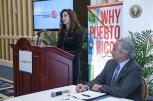 Renee Marie Stephano, president of the MTA (at podium) speaks at the event Tuesday, as Economic Development and Commerce Secretary Alberto Bacó looks on.