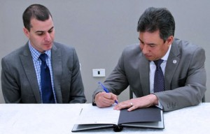 Edward Calvesbert Juliá, president of the board of directors of ABRE Puerto Rico and Manuel A. Torres Nieves, Electoral Comptroller, sign the agreement.