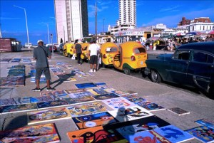 Paintings are spread out for sale at an outdoor flea market along Havana's oceanfront Malecón. (Credit: Larry Luxner)