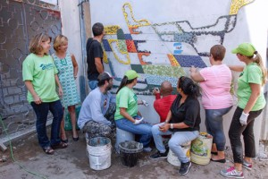 Amanda Silva, of Habitat and Carmen Pagán of FirstBank watch as the mural takes shape in Santurce.