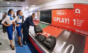 Casino Metro General Manager Ismael Vega picks up one of the suitcases as it landed on the numbers of the larger-than-life airport roulette.