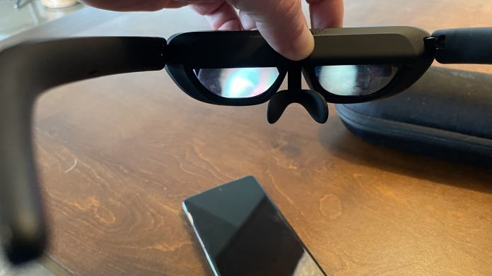 Person holding glasses by the top of the frame