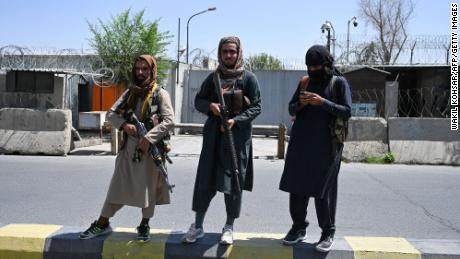 Taliban fighters stand guard along a street in Kabul on August 16, 2021.